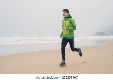 Young man running in the beach in a rainy day. Man is running on the sand.