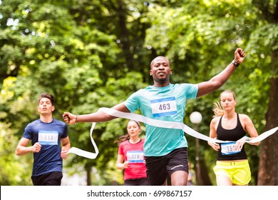 Young man running in the crowd crossing the finish line.