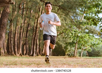 Young man running and doing workout outdoors at the park