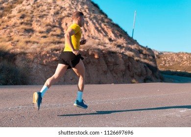 Young man running with greenish yellow shirt