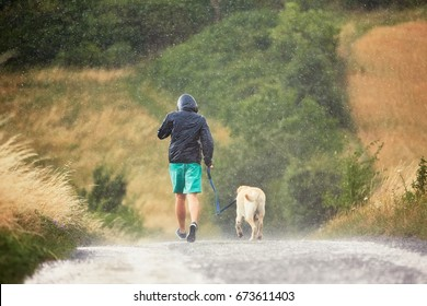 Young man running with his dog (labrador retriever) in heavy rain on the rural road.