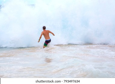 Young man running into the waves at the beach near Honolulu, Hawaii. Surfing huge waves. Oahu, USA. August 30, 2017