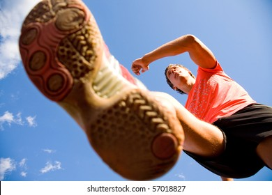 young man running lifting his feet high against the blue sky. Bottom view