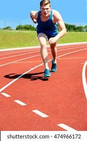 Young man running on athletics race track on stadium.