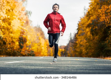 Young man running on the autumn road