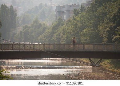 Young Man Running On Bridge In Wooded Forest Area - Training And Exercising For Trail Run Marathon Endurance - Fitness Healthy Lifestyle Concept