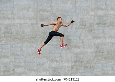 Young man running on grey background