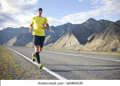 Young man running on mountain road. Amazing nature landscape.