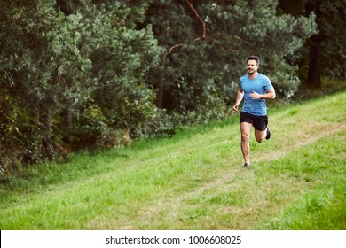 Young man running on path in park