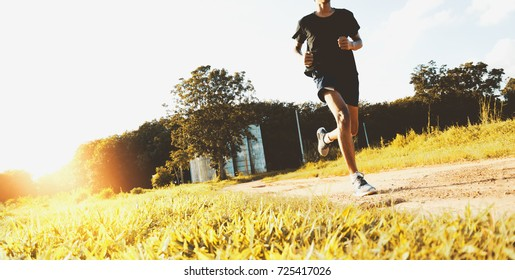 Young man running on a rural road during between the summer on vacation, Young man running according nature.