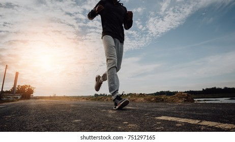 Young man running on a rural road during between the winter on vacation, Young man run according nature.