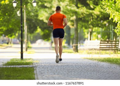 Young man running in park on sunny day