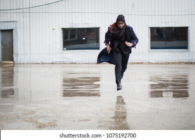 Young man running in the rain