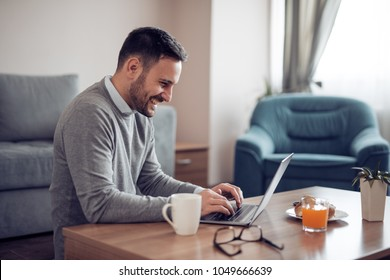 Young man running small business from home, working on laptop.