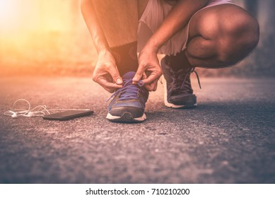 Young man running with smart phone on road behind sunset light background. - Vintage tone.