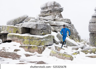 young man running in winter over stones on snow covered mountain trail