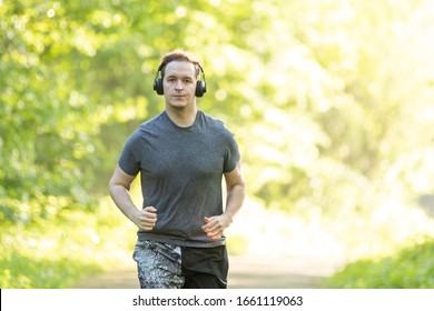 young man runs in a forest and makes fitness workout
