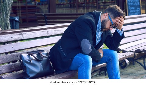 Young man with sad facial expression sitting on a bench in the park. Office worker lost his job. Middle aged man despair economic crisis.