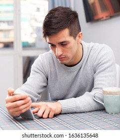 Young man is sad sitting with phone because she is alone at home