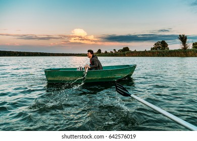 Young man sailing boat on the river, sunset