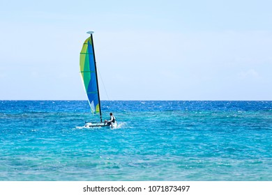 young man sailing a catamaran, active vacation concept, copy space on right