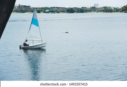 Young man sailing. man on yacht sailboat on marsh, swamp. Healthy water sport. Yachting class for sport man sailor.
