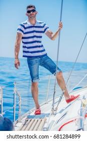 Young man sailing yacht. Sail vacation. People holidays travel