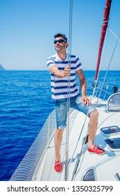 Young man sailing yacht steering wheel vacation sail. Holidays, people, travel