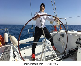 Young man sailing yacht steering wheel vacation sail holidays people travel