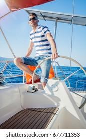 Young man sailing yacht steering wheel vacation sail holidays people travel