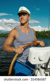 Young man sailor at the helm of yacht. Summer time.