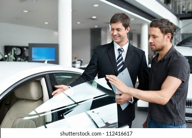 Young man with a salesman in a motor show