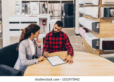 Young man with saleswoman in large modern household appliances store signing contract.