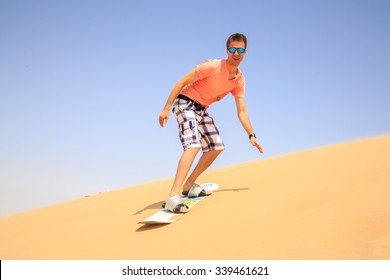 Young man sand boarding in a desert down the dune near Emirates