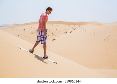 Young man sand boarding in a desert down the dune in Sahara