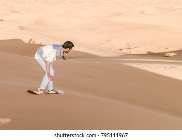 Young man sand boarding in the Dubai desert sand dunes