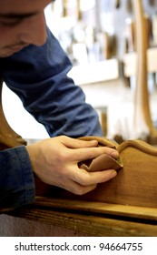 Young man sanding furniture