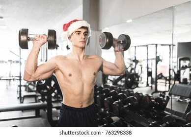 Young man with Santa Claus Christmas hat training shoulder exercise in gym after christmas