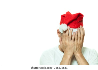 Young man with Santa Claus hat cover his face with his hands feeling lonely and sad for New Year and Christmas holiday depression concept