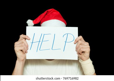Young man with Santa Claus hat cover his face with help sign after suicidal attempt feeling lonely and sad for New Year and Christmas holidays depression concept isolated on black background