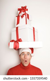 Young man in Santa hat and red turtleneck balancing a tower of Christmas presents on his head