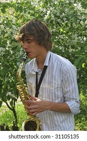 the young man with saxophone on the background of the flowering tree