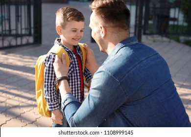 Young man saying goodbye to his little child near school