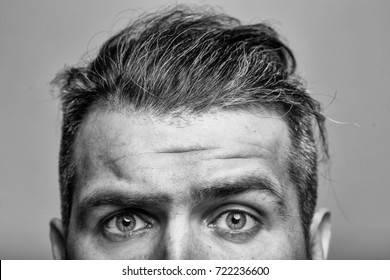young man with scared eyes on emotional face with long hair in studio on grey background