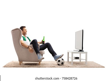 Young man with a scarf and a bottle of beer sitting in an armchair and watching football on TV isolated on white background