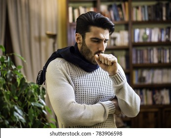 Young man with scarf coughing and holding his neck because of cold and throat-ache, at home in his living room