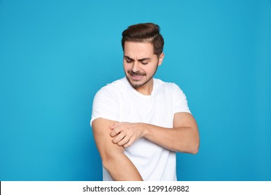 Young man scratching arm on color background. Annoying itch