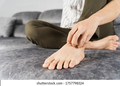 Young man scratching foot while sitting on sofa at home. Healthcare medical or daily life concept.