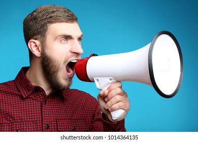 Young man screaming in megaphone on blue background