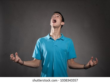 young man screaming on a grey background